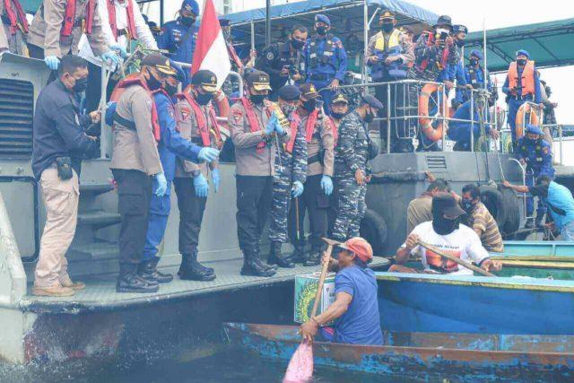 Personel dari Polda Kalimantan Timur dan Lanal Balikpapan membagikan bantuan stimulus bagi warga pesisir dan nelayan di Pantai Lango