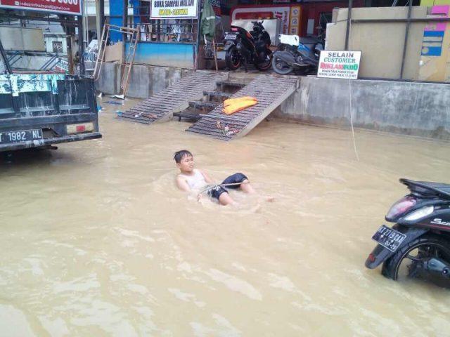 Jadi Kolam Renang, Jalan Mayjen Sutoyo Dimanfaatkan Anak-Anak - headlinekaltim